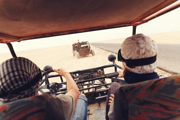 Pareja joven montando coche buggy en el desierto Foto Premium