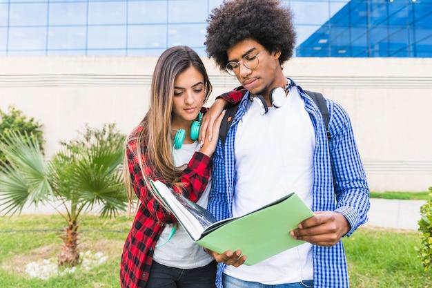 Pareja joven multiétnica junto leyendo el libro de pie contra el edificio de la universidad Foto gratis