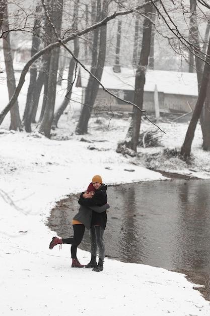 Pareja joven en paisaje de invierno con árboles y lago Foto gratis