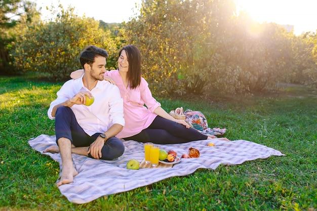 Pareja joven en el parque al aire libre haciendo un picnic Foto gratis