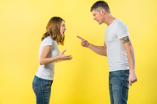 Pareja joven de pie cara a cara discutiendo entre sí contra el fondo amarillo Foto gratis