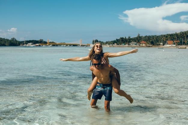 Pareja joven posando en la playa, divirtiéndose en el mar, riendo y sonriendo Foto gratis