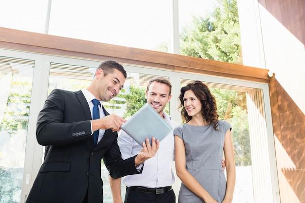 Pareja joven reunión inmobiliaria mostrando un proyecto de casa en una tableta digital Foto Premium
