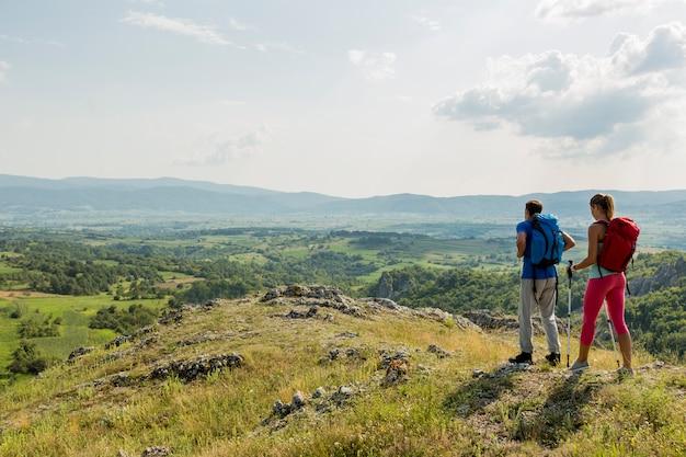 Pareja joven de senderismo en la montaña Foto Premium