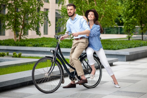 Pareja joven sentada en una bicicleta frente al parque verde de la ciudad Foto gratis