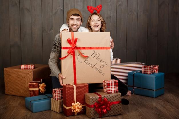 Pareja joven sentada entre cajas de regalo de navidad sobre superficie de madera Foto gratis