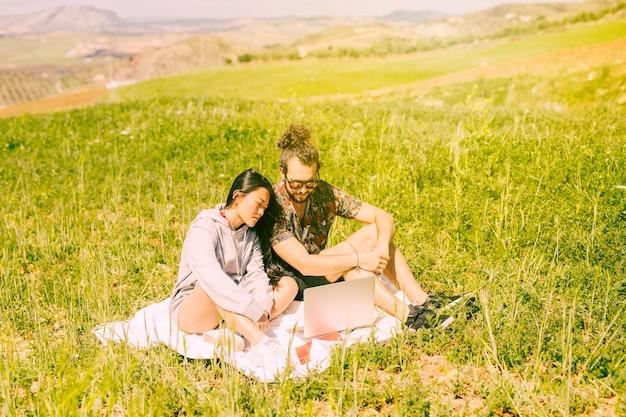 Pareja joven sentada en el campo con el portátil Foto gratis