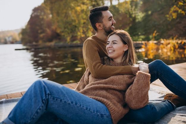 Pareja joven sentada en el puente de cubierta junto al río Foto gratis