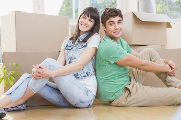 Pareja joven sentados juntos en el piso y sonriendo en su nueva casa Foto Premium