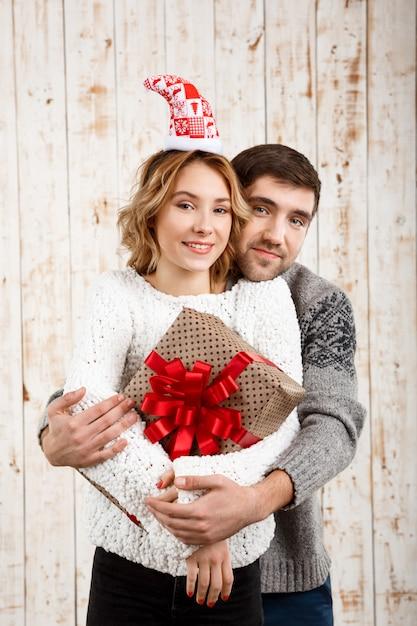Pareja joven sonriendo abrazando la celebración de regalo de navidad sobre superficie de madera Foto gratis