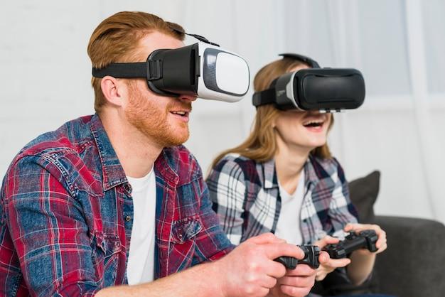 Pareja joven sonriente con gafas de realidad disfrutando de jugar el videojuego Foto gratis