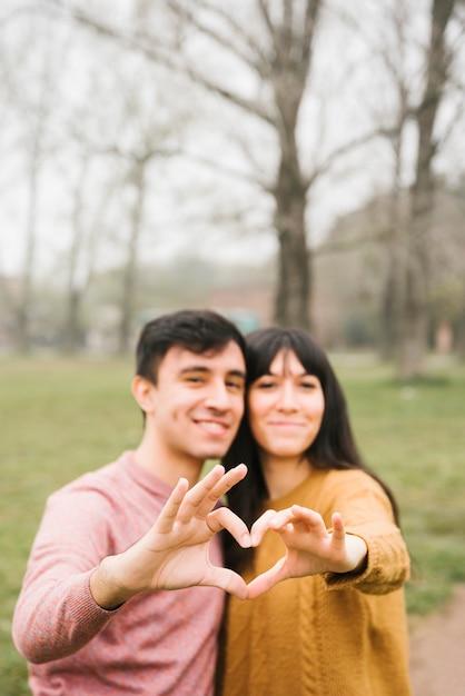 Pareja joven sonriente que abraza mostrando gesto del corazón Foto gratis