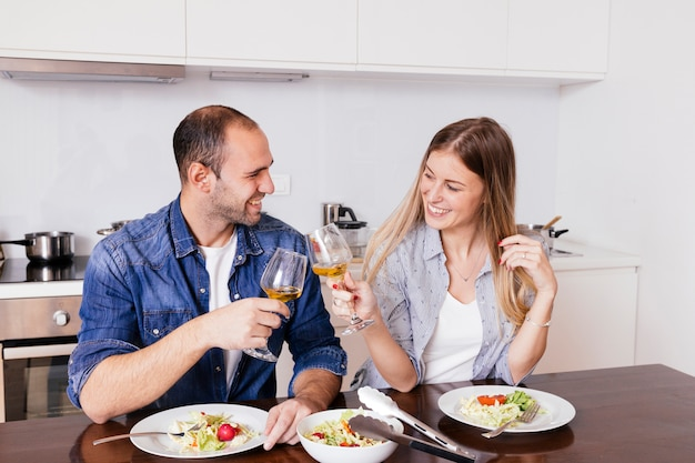 Pareja joven sonriente que come la ensalada que tuesta con las copas de vino en la cocina Foto gratis