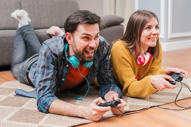 Pareja joven sonriente que miente en el piso que juega al videojuego con la palanca de mando en casa Foto gratis