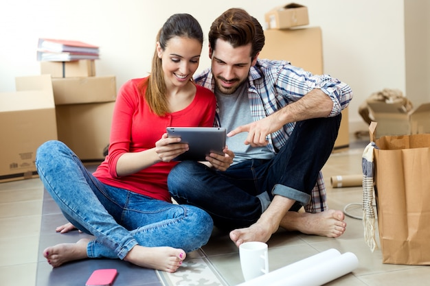 Pareja joven con tableta digital en su nuevo hogar Foto gratis