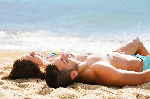 Pareja joven tendido en la playa de arena en la orilla del mar Foto gratis