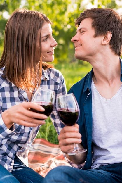 Pareja joven tintineando copas de vino fuera Foto gratis