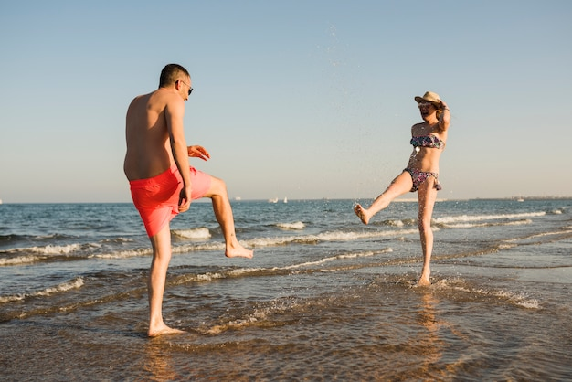 Pareja joven en traje de baño salpicando el agua en la playa Foto gratis
