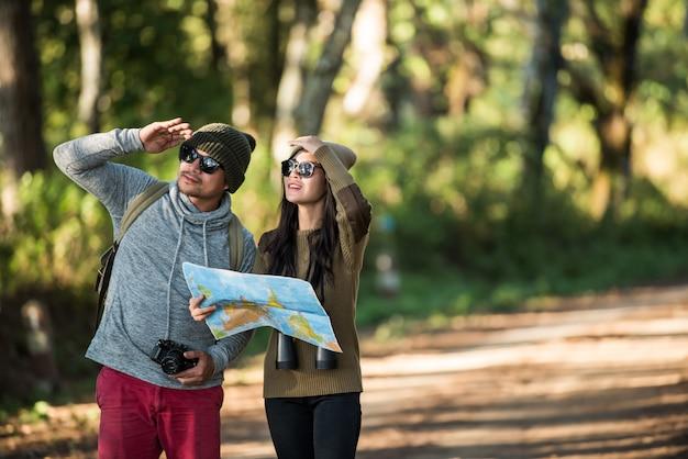 Pareja joven turista viaja en bosque de montaña Foto gratis