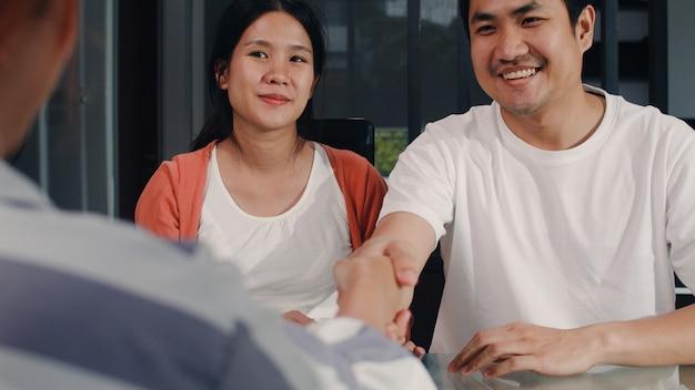 Pareja de jóvenes embarazadas asiáticas firma documentos de contrato en el hogar, una familia japonesa consulta con un asesor financiero inmobiliario, compra una casa nueva y un apretón de manos con un corredor en la sala de estar por la mañana. Foto gratis