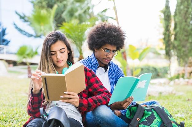 Pareja de jóvenes sentados juntos en el césped leyendo un libro en el parque al aire libre Foto gratis