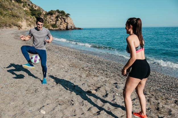 Pareja Jugando Al Futbol En La Playa Descargar Fotos Gratis