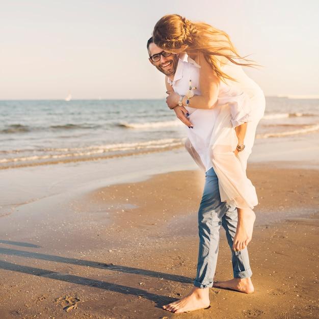 Pareja juguetona en la playa del océano disfrutando de sus vacaciones de verano Foto gratis