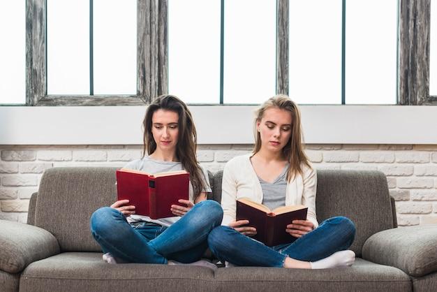 Pareja de lesbianas jóvenes sentados en un sofá gris con las piernas cruzadas leyendo un libro Foto gratis