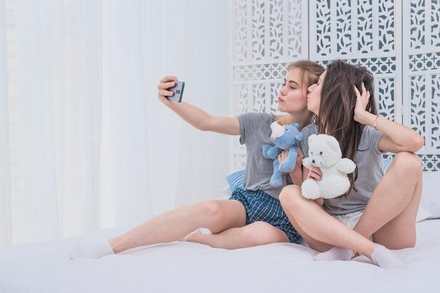 Pareja de lesbianas sentadas en la cama sosteniendo peluches tomando selfie en un teléfono móvil Foto gratis