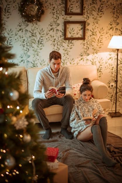 Pareja leyendo libros en casa Foto gratis