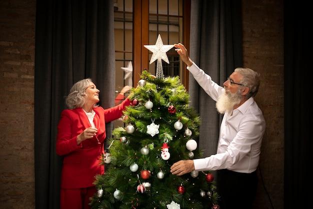 Pareja mayor, configuración, árbol de navidad Foto gratis