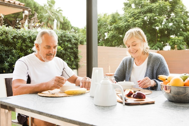 Pareja mayor desayunando en jardín Foto gratis