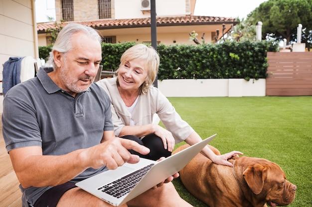 Pareja mayor con perro en jardín Foto gratis