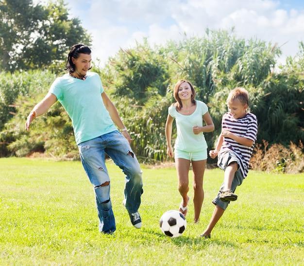 Pareja De Mediana Edad Y Adolescente Jugando Con Balon De Futbol