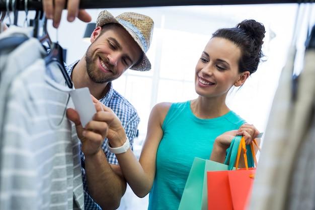 Pareja mirando la etiqueta de precio de la ropa Foto gratis