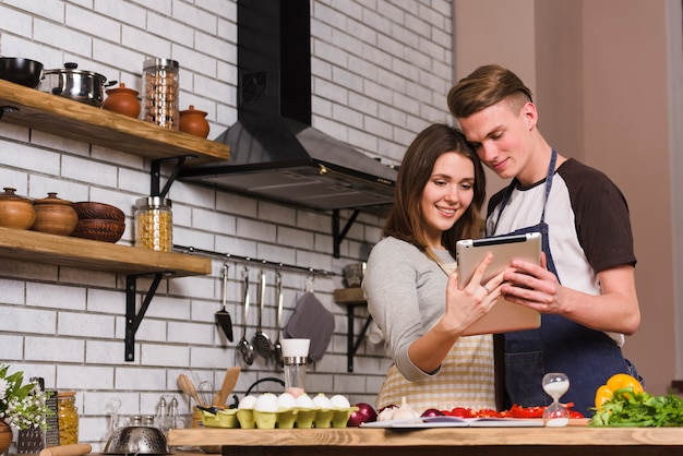 Pareja mirando la tableta mientras se abraza en la cocina Foto gratis