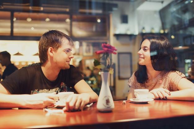 Pareja mirándose sentada en un bar Foto Premium