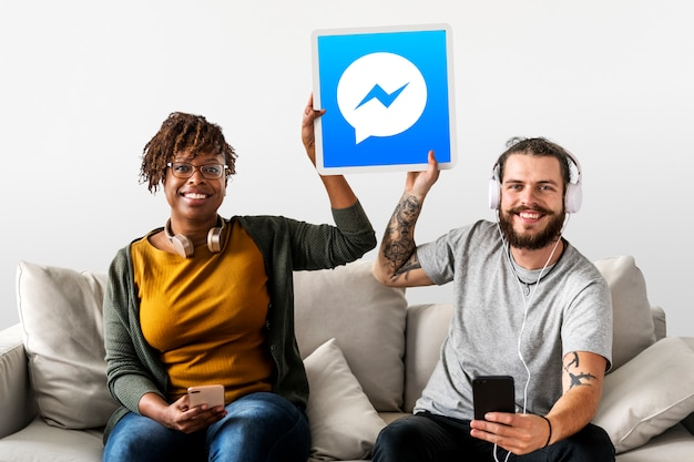 Pareja mostrando un icono de facebook messenger Foto gratis