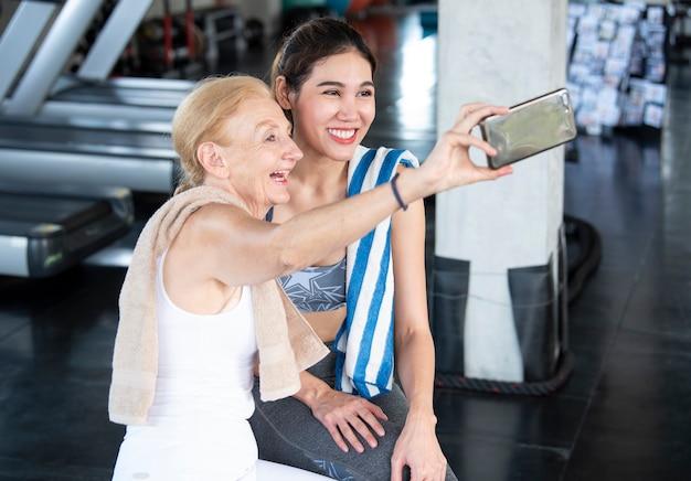 Pareja de mujeres atractivas sonriendo tomando un selfie en smartphone en gimnasio fitness. Foto Premium
