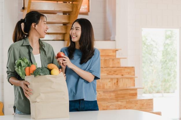 Pareja de mujeres lgbtq lesbianas asiáticas tienen bolsas de papel de compras en el hogar Foto gratis