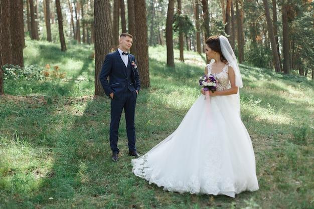 Pareja de novios emocional en el parque verde en primavera. novia y el novio en un día soleado al aire libre. día de la boda en la naturaleza en un día soleado Foto Premium