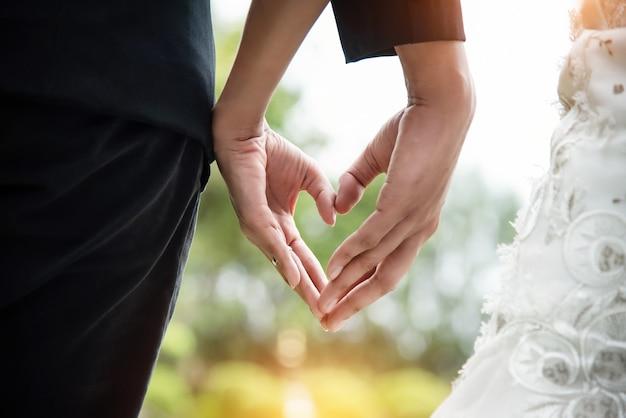 7a8a387d4 La pareja de novios está haciendo el signo de la mano de amor juntos ...