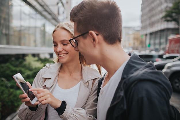 Pareja o amigos riendo divertido y divirtiéndose con un teléfono inteligente en una calle de la gran ciudad. Foto Premium