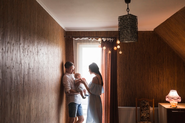 Pareja de pie cerca de la ventana jugando con su bebé en casa Foto gratis