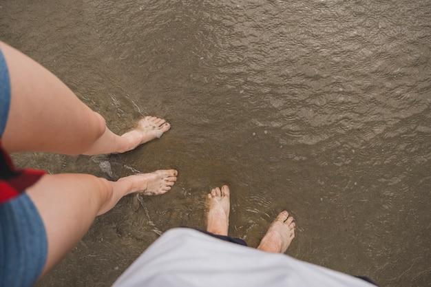 Pareja de pies descalzos sobre el agua en la playa Foto gratis
