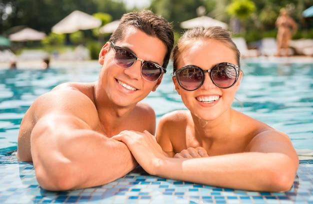 Pareja en la piscina del complejo. mirando a la camara Foto Premium