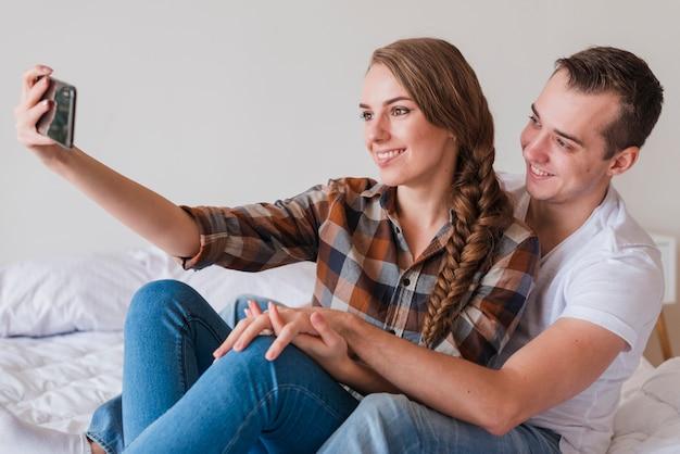 Pareja positiva joven tomando selfie en dormitorio en casa Foto gratis