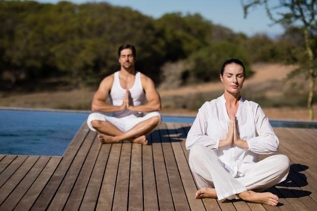 Pareja realizando yoga en vacaciones de safari Foto gratis