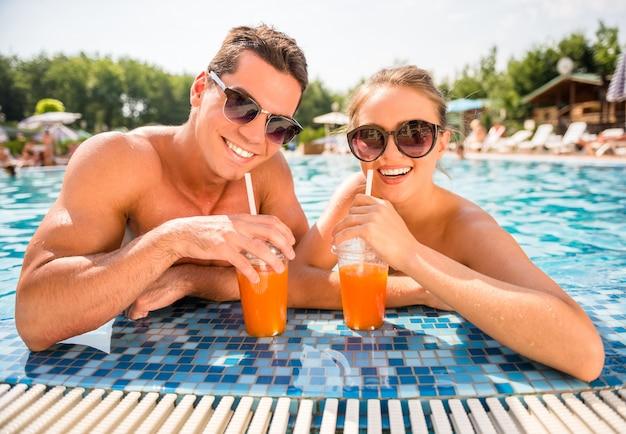 Pareja relajante en la piscina del complejo, tomando cócteles. Foto Premium