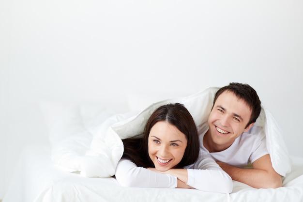 Pareja riéndose en la cama Foto gratis